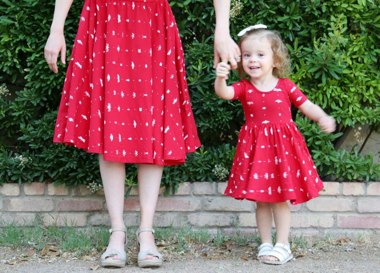 Little Girl Twirling in a Red Dress with Mommy